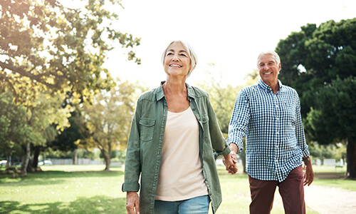 A man and woman walking through the park and smiling