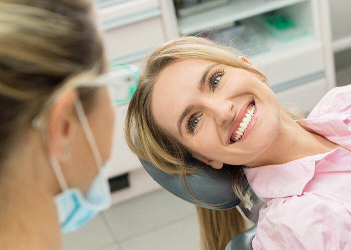 A patient smiling and looking at dental staff on patient room