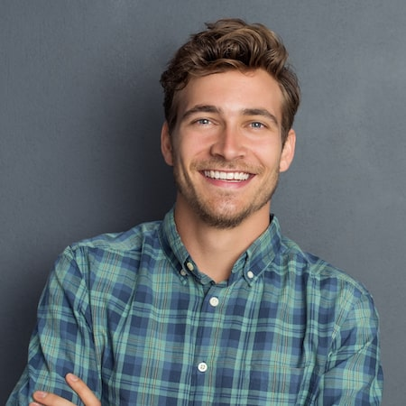 Man standing in front of a grey wall and smiling