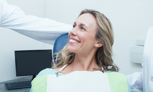 Woman smiling the dentist chair and wearing a dental bib