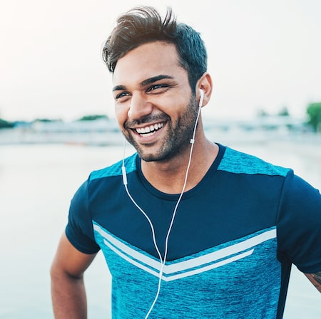 Man in sports gear listening to headphones and smiling because of the exceptional Seattle family dentistry he receives at SeattleScape Smiles.