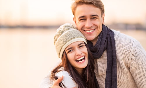 Younger couple hugging outside with winter clothes on