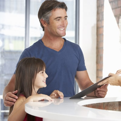 Man with his daughter holding a clipboard and smiling
