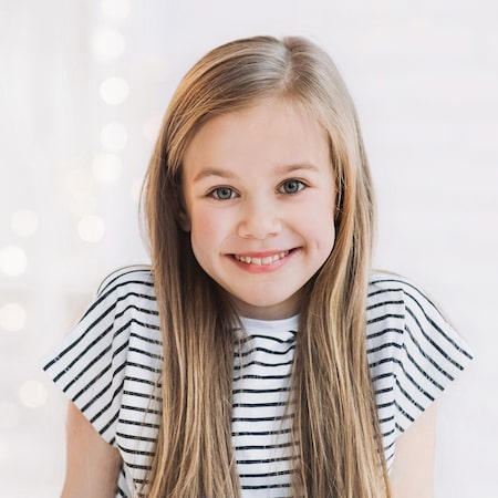 Little girl in a striped top smiling in front of a light background