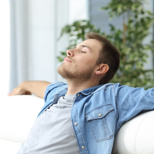 Man in a jean shirt relaxing on the sofa with his arms outstretched