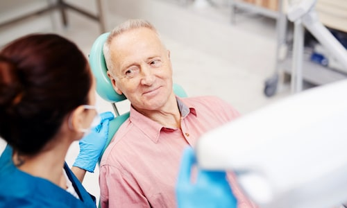 Older male patient sitting in the dentist chair and listening to one of our team members