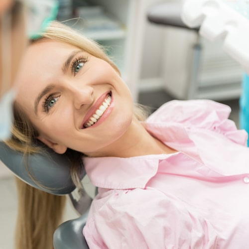 Female patient in a pink shirt sat in the dental chair and smiling as she receives Seattle family dentistry at SeattleScape Smiles.
