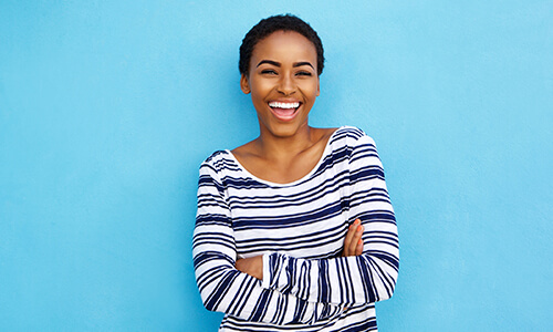 Image of a young woman laughing with her arms crossed