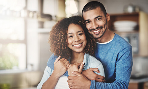 Image of a young couple hugging and smiling indoors