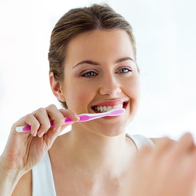 Woman brushing her teeth after removing her Invisalign aligners