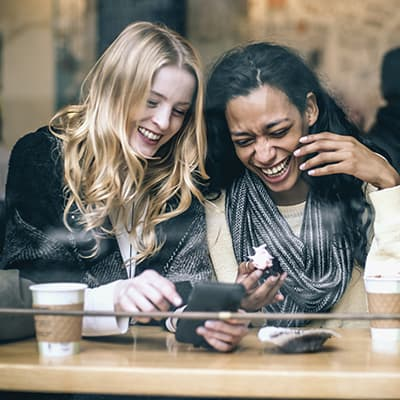 Women laughing in a Seattle coffee shop getting orthodontic treatment